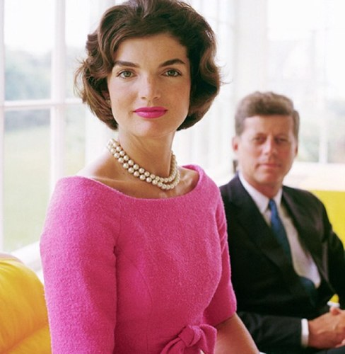 Jackie Kennedy in foreground and John F. Kennedy in background.