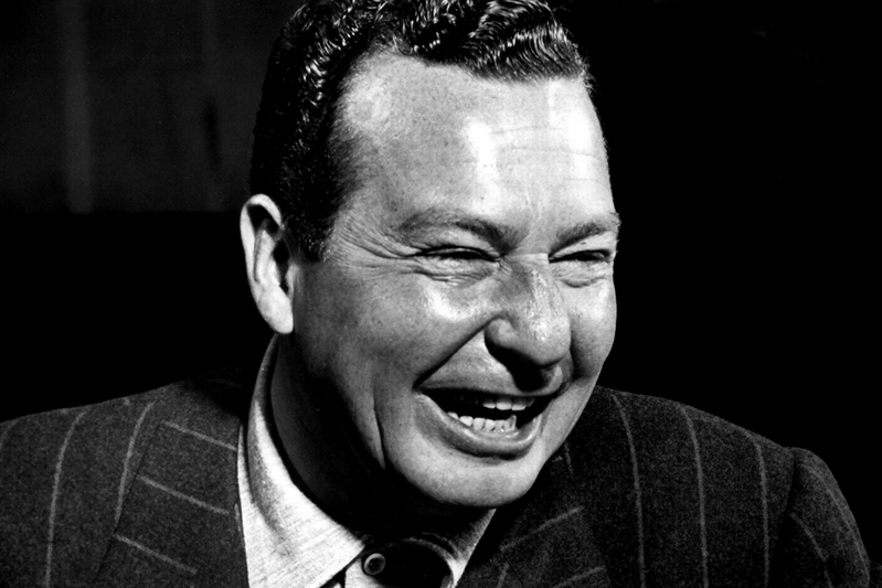 Phil Harris smiles in a pin striped suit.