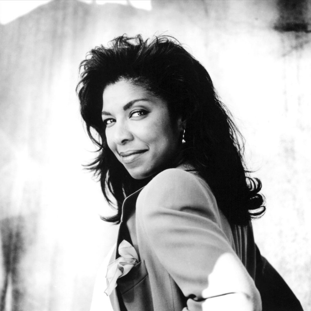 Natalie Cole looks over her should with windswept hair and a sly smile.