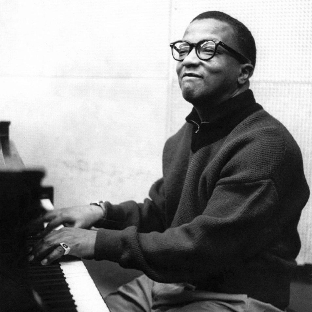 Billy Strayhorn plays the piano with a mischievous look.