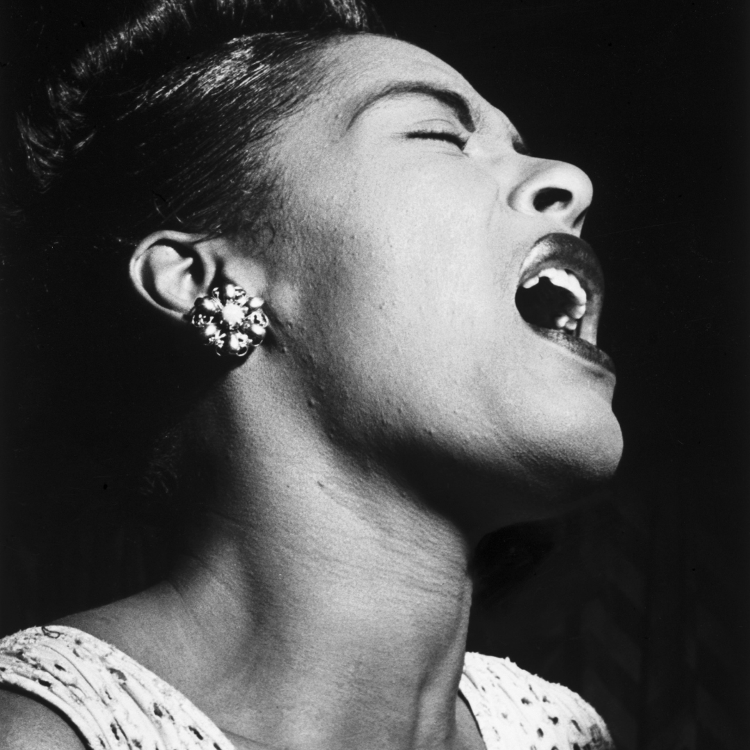 Billie Holiday throws her head back and sings with an entranced expression on her face.