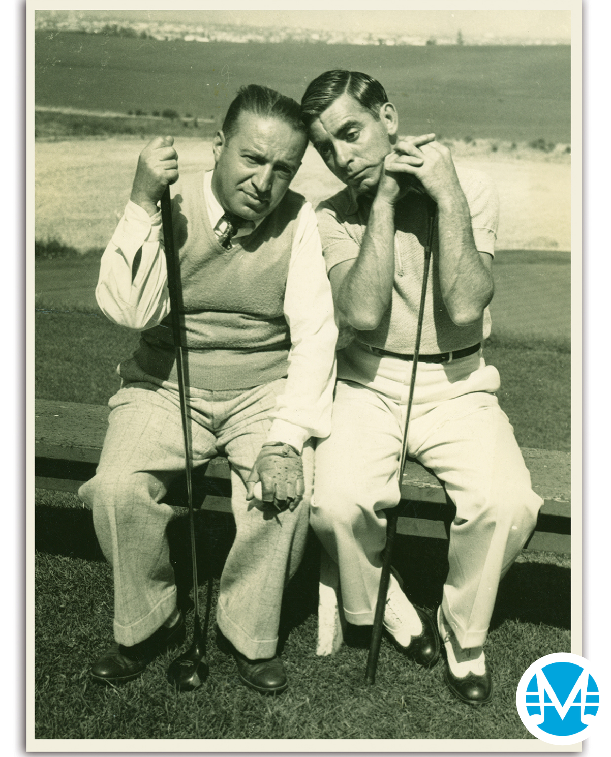 Gus Kahn and Eddit Canto pose with silly faces and hold golf clubs.